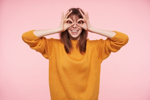 Young cheerful dark haired woman dressed in casual clothes making faces while standing over pink wall with raised hands and smiling joyfully