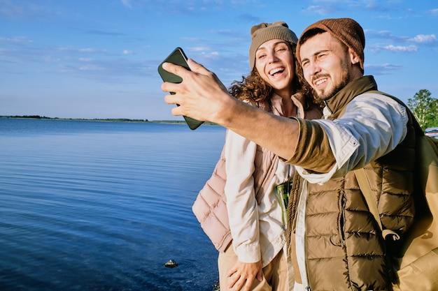 Молодые веселые свидания стоят друг рядом с другом и смотрят в камеру смартфона, делая селфи на фоне голубого неба и воды