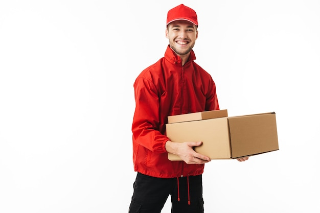 Young cheerful delivery man in red cap and jacket holding boxes in hands happily