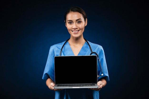 Young cheerful doctor showing blank screen of laptop computer isolated