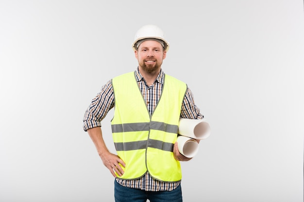 Young cheerful engineer or foreman in protective helmet and workwear holding rolled blueprints in isolation