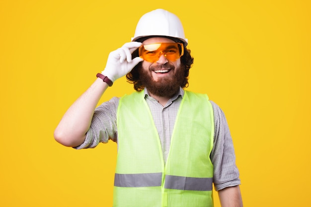 Young cheerful engineer is smiling at the camera and holding a pair of protective glasses is standing near a yellow wall