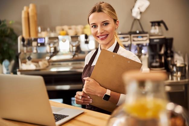 Молодой веселый предприниматель, держа в руках буфер обмена в кафе