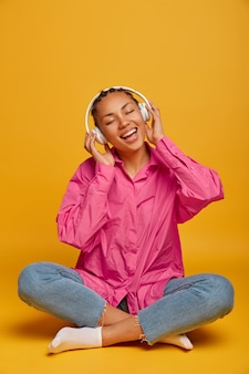 若い陽気な民族の女性は床で音楽を楽しんで、足を組んで座って、ピンクのシャツ、ジーンズ、靴下を着て、黄色い壁に隔離され、上の空きスペースで大きな音でオーディオトラックを聴きます