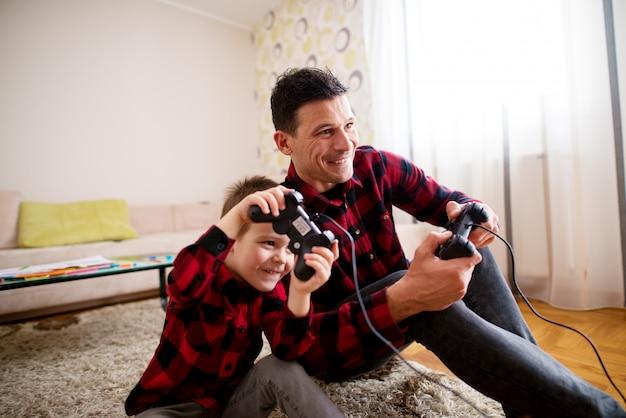 Молодой веселый возбужденный отец и сын в одной красной рубашке играют в консольные игры с геймпадами, прислонившись друг к другу в светлой гостиной.