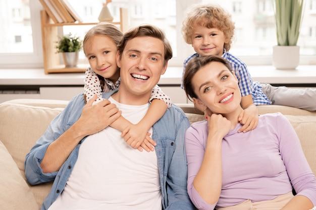 Молодая веселая семья отца, матери и двух милых братьев и сестер обнимаются во время отдыха на диване