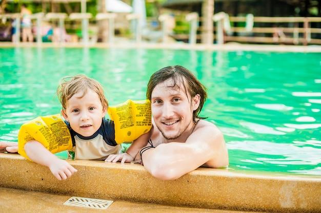 若い陽気な父と息子のスイミングプール