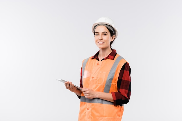 Young cheerful female engineer in helmet and orange jacket using touchpad while standing in isolation
