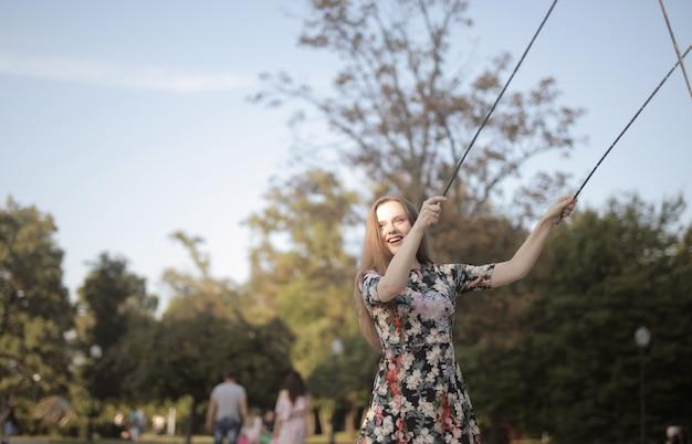 Молодая веселая женщина в парке под солнечным светом