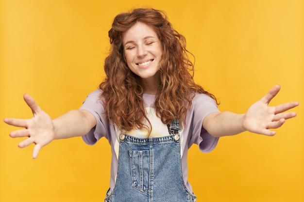 若い陽気な女子学生は、青いデニムのオーバーオールと紫色のtシャツを着て、幸せを感じ、広く笑顔で、彼氏と抱きしめたいと思っています。黄色の壁に隔離
