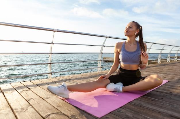 若い陽気なフィットネス女性は、ビーチのマットに座って音楽を聴きます。