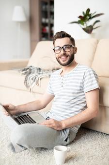 Молодой веселый фрилансер в полосатой футболке и спортивных штанах сидит на полу и работает в сети дома