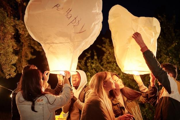 Молодые веселые друзья в теплой повседневной одежде смотрят внутрь больших белых воздушных шаров с подсветкой, веселятся на вечеринке на открытом воздухе
