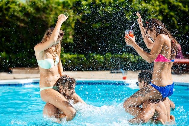 Юные веселые друзья улыбаются, смеются, отдыхают, купаются в бассейне