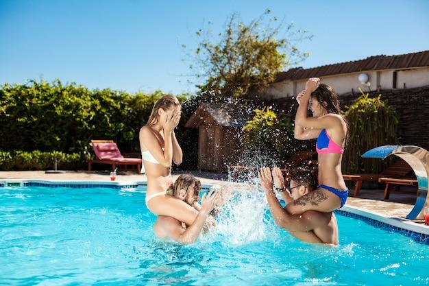 笑顔、笑い、リラックス、プールで泳いでいる若い陽気な友人
