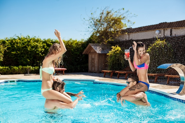 Young cheerful friends smiling, laughing, relaxing, swimming in pool