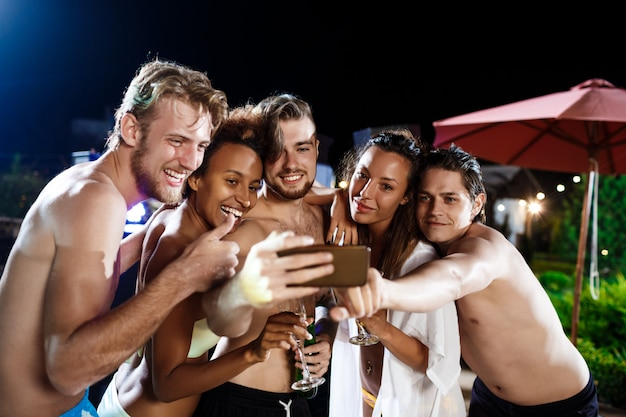 Young cheerful friends smiling, rejoicing, making selfie, resting at party