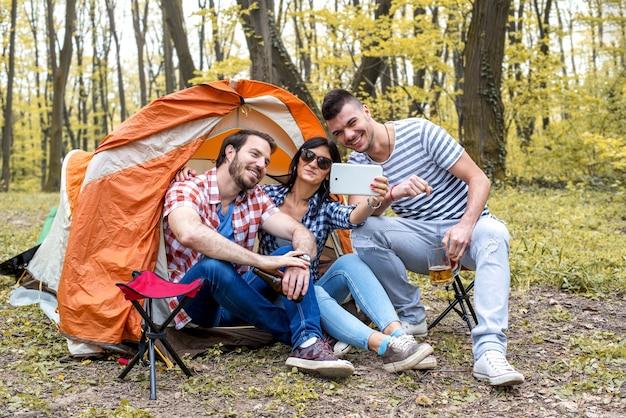 ピクニックをしながら写真の自分撮りを撮る若い陽気な友達 Premium写真
