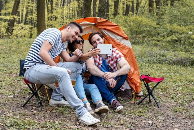 Young cheerful friends taking photo selfie while doing a picnic