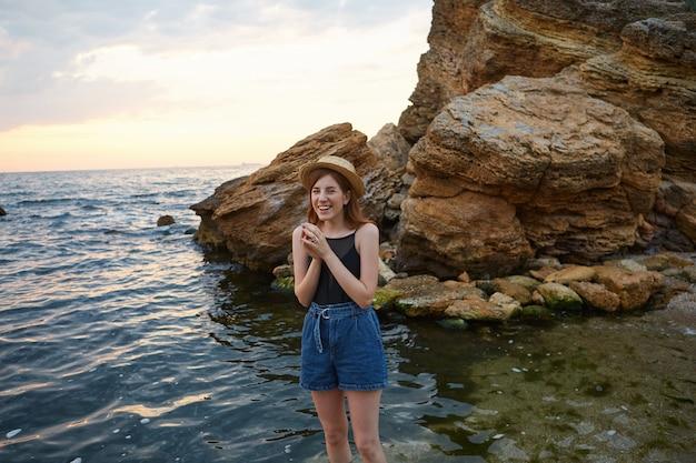 帽子をかぶった若い陽気な生姜そばかすの女性は、広く笑顔で海辺で朝を楽しんで、前向きで幸せそうに見えます。