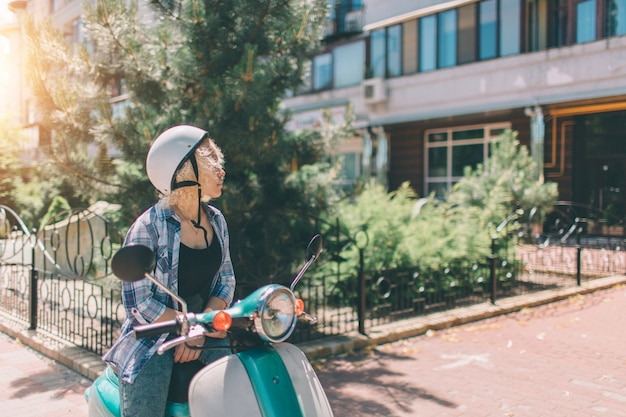 Young cheerful girl driving scooter in in city. portrait of a young and stylish woman with a moped