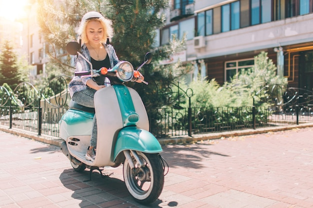 Young cheerful girl driving scooter in in city