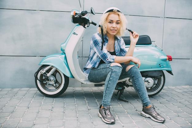 Молодая жизнерадостная девушка управляя самокатом внутри в городе. портрет молодой и стильной женщины с мопедом
