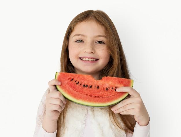 Молодая веселая девочка держит кусок арбуза