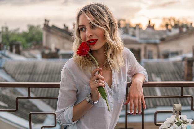 Молодая веселая девушка держит красный цветок на балконе или крыше. время заката