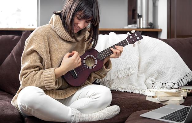 Молодая жизнерадостная девушка в свитере учится играть на гавайской гитаре. концепция онлайн-обучения, домашнего образования.
