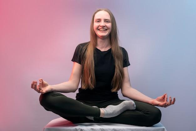 Молодая веселая девушка медитирует