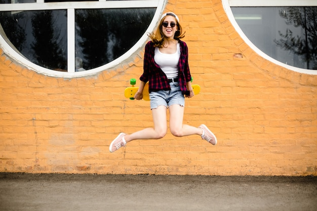 Young cheerful girl posing with yellow skateboard against orange wall.