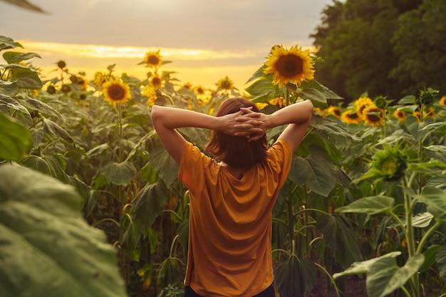 젊은 쾌활한 소녀는 해바라기 들판 사이에 혼자 서서 전망을 감상하며 순간 수확 시간을 즐깁니다.