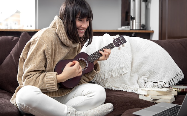 Young cheerful girl in a sweater learns to play the ukulele. concept of online learning, home education.