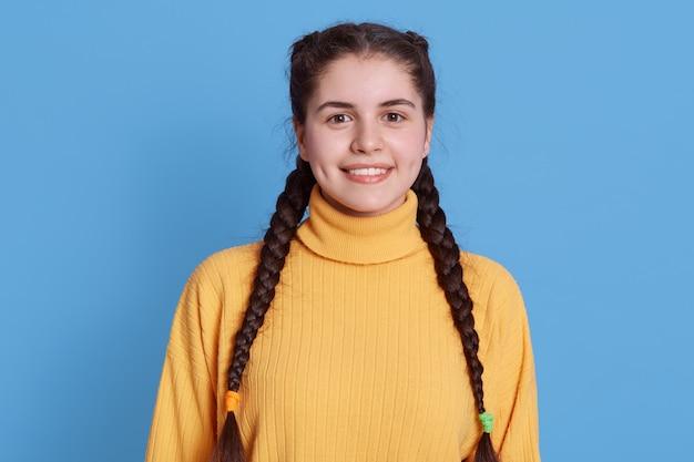 冬の居心地の良い黄色のセーターを着て、歯を見せる笑顔で正面を見て、黒い髪とおさげ髪をして、青い壁に立っている若い陽気な女の子