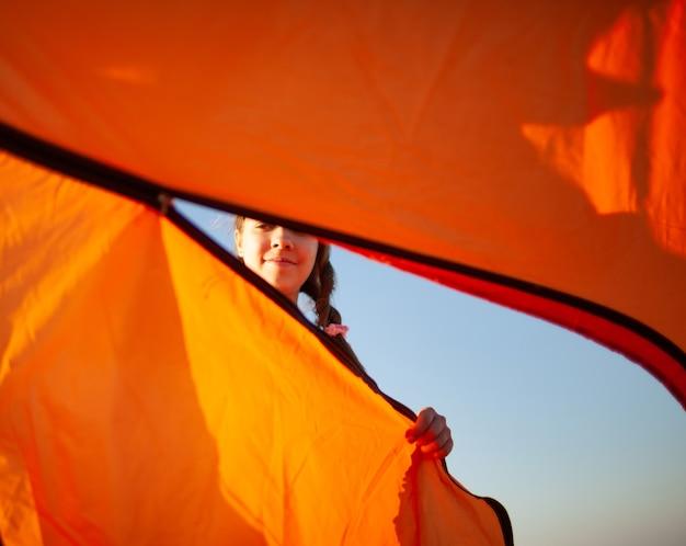 Молодая веселая девушка в темноте закрывает яркую палатку, глядя на свои осторожные действия на берегу синего моря в прекрасный вечер