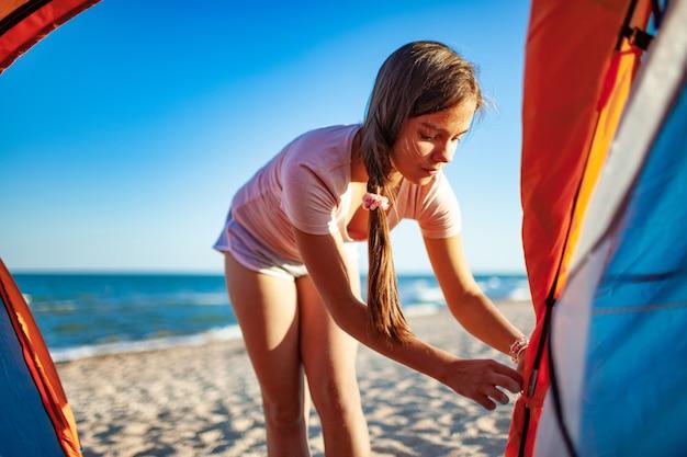 어두운 명랑 소녀는 아름다운 저녁에 푸른 바다 해안에 그녀의 신중한 행동을보고 밝은 텐트를 닫습니다