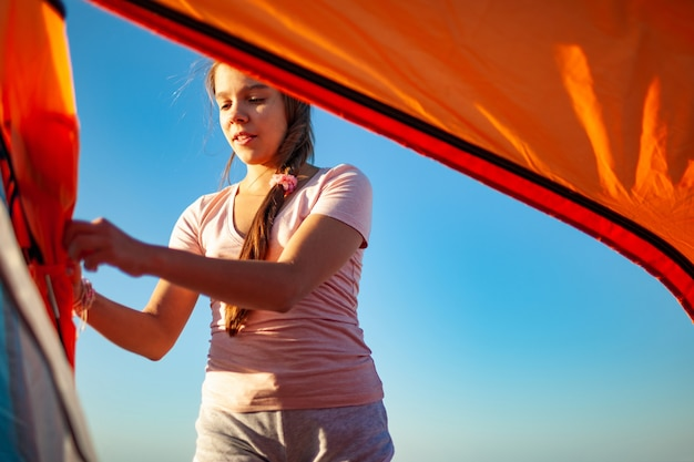 Young cheerful girl with dark closes a bright tent looking at her cautious actions on the blue sea shore on a beautiful evening