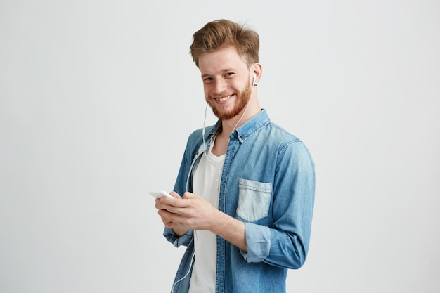 Young cheerful guy in headphones smiling holding phone listening to music.
