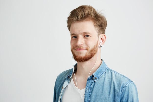 ストリーミング音楽を聴いて笑っているヘッドフォンで若い陽気な男。