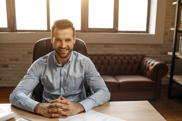 Young cheerful handsome businessman sit at table and pose in his own office. he look straight on camera and hold hands on table.