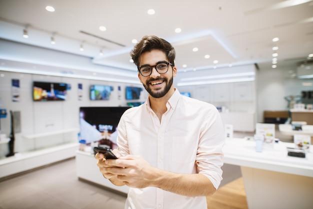 Молодой веселый красавец в белой рубашке использует телефон в очень яркий технический магазин.