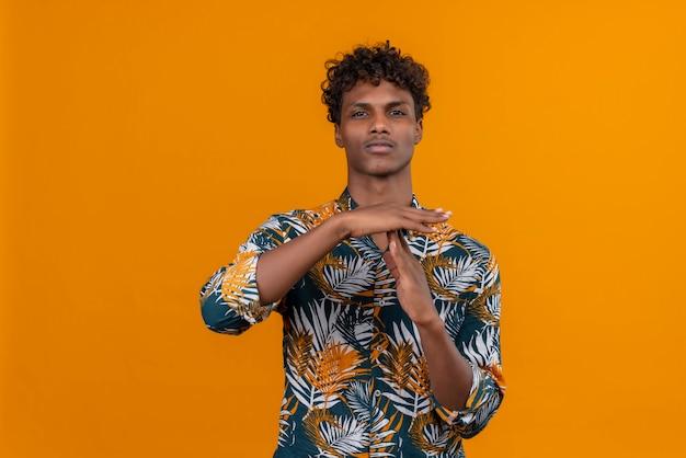 Молодой веселый красавец показывает жест тайм-аута руками на оранжевом фоне