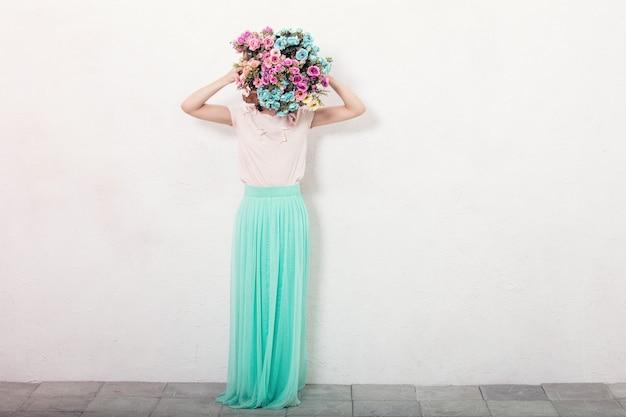 흰 벽 바탕에 꽃이 있는 치마를 입은 젊고 쾌활한 행복한 아름다운 여성