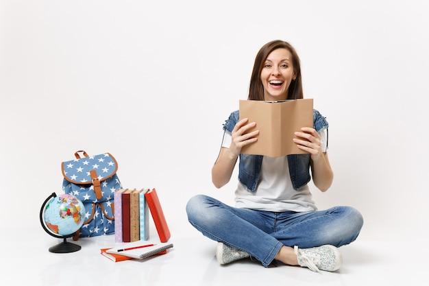 Giovane studentessa felice allegra in vestiti di denim che tiene la lettura del libro seduta vicino al globo, zaino, libri di scuola isolati