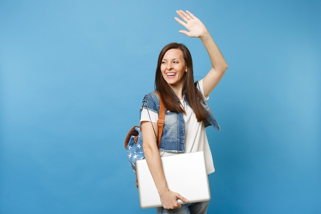 Young cheerful happy woman student with backpack waving hand for greeting, meeting friends holding laptop pc computer isolated on blue background. education in college. copy space for advertisement.