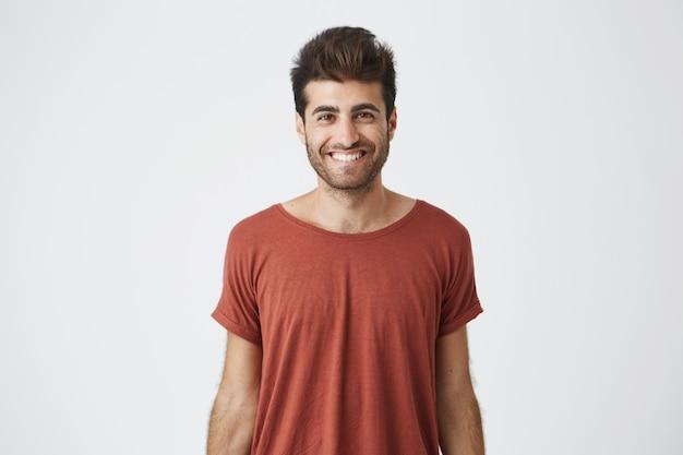 Giovane ragazzo ispanico allegro in maglietta rossa che sorride brillantemente sentendo buone notizie dall'amico. studente barbuto bello con sorriso gioioso