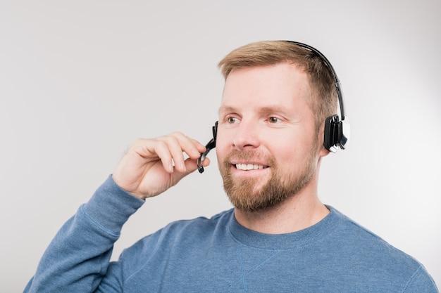 Молодой веселый оператор горячей линии в гарнитуре и синем пуловере консультирует клиентов во время разговора в микрофон