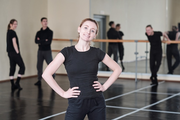 Young cheerful instructor of modern dancing course standing in akimbo posing