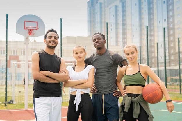 バスケットボールの遊び場やスタジアムで互いに近くに立っているアクティブウエアで陽気な異文化の若い友人